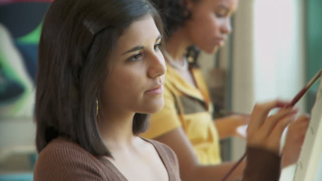 TU, PAN, CU, Teacher talking to student (14-15) painting in art class, Richmond, Virginia, USA