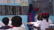 Teacher teaching her school students in a classroom