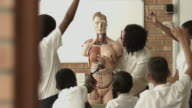 Teacher teaching in biology class, using torso