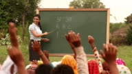 Teacher teaching to rural people, Haryana, India