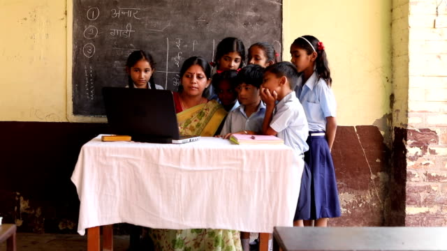 Teacher teaching to school students in classroom, Haryana, India