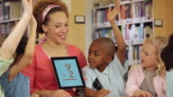 MS Teacher Using Math Flash Cards on Tablet Computer with Students in Library / Richmond, Virginia, USA