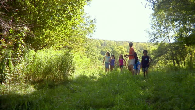 MS, teacher walking with children (8-11) across meadow, Bovina, New York State, USA