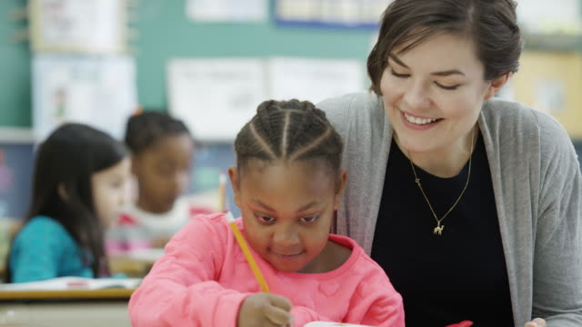 Teacher works with her elementary school students in class