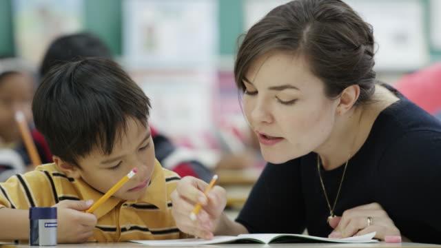 Lehrer arbeiten mit ihr Grundschule Schüler in Klasse