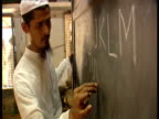 Teacher writes English alphabet on backboard with chalk
