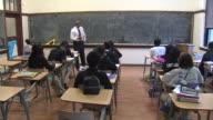 WGN Teacher writing on blackboard at St Mel High School on February 25 2014 in Chicago Illinois