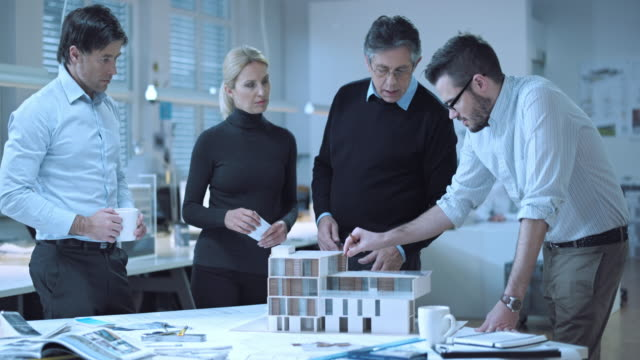 DS Team of architects brainstorming around the model