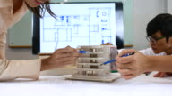 Team of Architects defining detail of architectural model in office