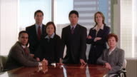 A team of business professionals poses in a conference room.