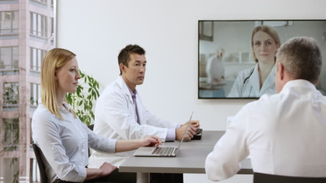 Team of physicians on a videoconference call with a female colleague