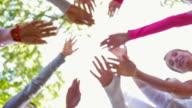 Team di raggiungere nella tattica per celebrare la prima gara di corsa for breast cancer awareness
