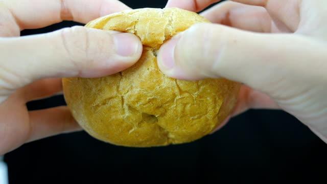 Zerreißen Brot mit Händen. Vorderseite. Nahaufnahme. Zeitlupe.