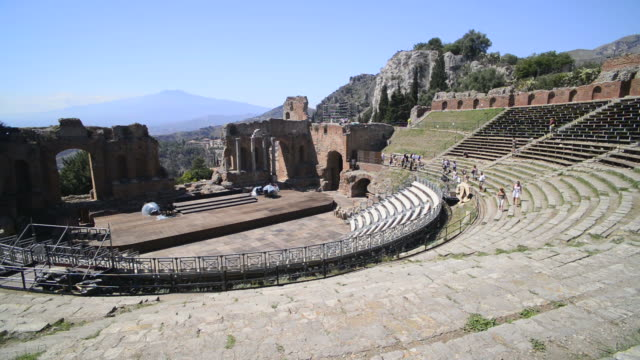 Teatro Greco aka Taormina Greek Theatre, tourists sightseeing at the amphitheatre with Mount Etna Volcano behind, Sicily, Italy, Europe