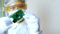 Technician holding and investigating micro controller board in clean room