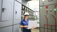 Technician inspects industrial control room.