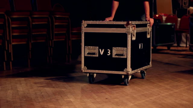 Technician / Roadie pushes a flightcase on stage
