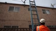 A DIRECTV technician unloads a ladder while installing new satellite TV service at an apartment in Lynwood California US A DIRECTV technician...