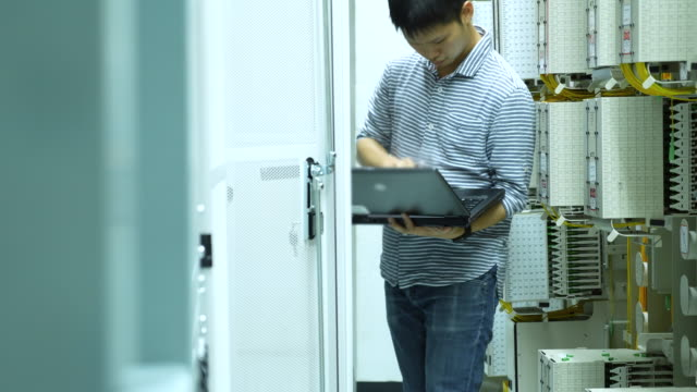 Technician working on laptop in the Wired Network room