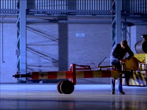 Technicians attach tow bar to wheel of aircraft in hangar