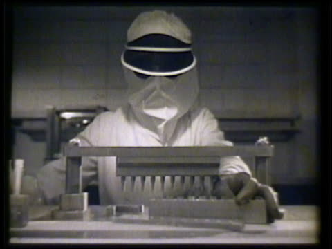 Technicians in full laboratory suits checking antibiotic samples in small test tubes moving on conveyor belt VS Placing tray of test samples under...