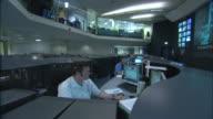Technicians wearing headphones monitor traffic on computer screens.