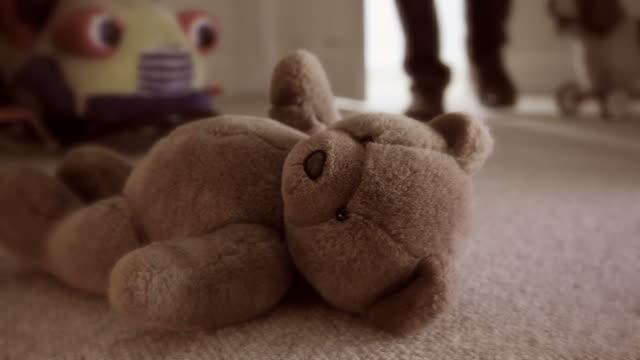 Teddy bear on bedroom floor.