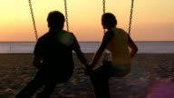 Teen boy and girl sitting on swings at the beach holding hands as the sun goes down