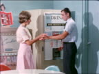 1963 teen boy getting cup of soda from vending machine + handing it to girl / gets one for himself