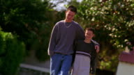 CANTED teen boy walking with arm around shorter boy outdoors / boys look at each other + smile