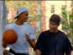 2 teen boys (1 Black) with basketball walking in city park towards camera / East Village, NYC
