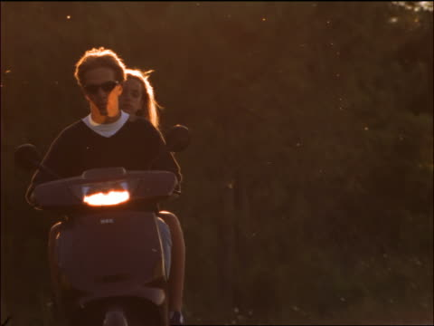 Teen couple riding moped towards camera / Corsica
