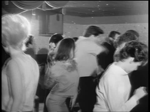 B/W 1965 PAN teen couples dancing in nightclub as Black rock band performs on stage / newsreel