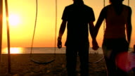 Teen girl and boy leaving the swings walking hand in hand on the beach at sunset