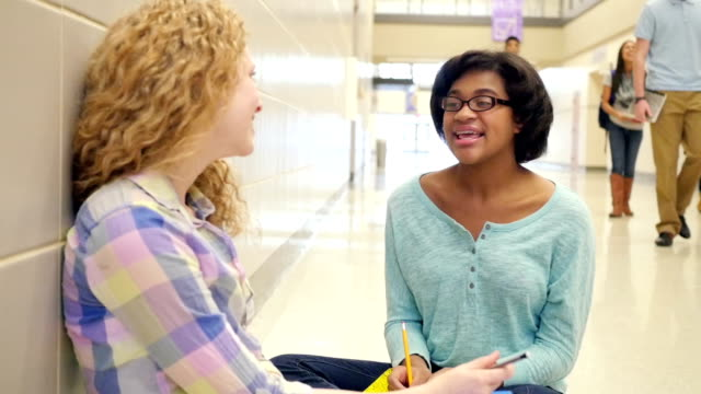 Teen girls sitting in hallway of high school and talking after class
