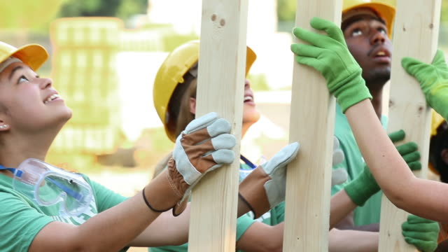 teen volunteers lifting construction framing