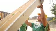 teen volunteers lifting construction framing