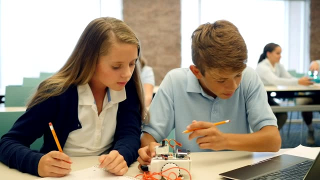 Teenage boy and girl work together on robotics project in technology class