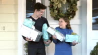 Teenage boy and little sister holding Christmas gifts