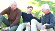 Teenage boy conversing with father and grandfather