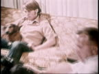 1973 MONTAGE teenage boy, dog, and dad sitting on couch watching television, dad asking about election / United States