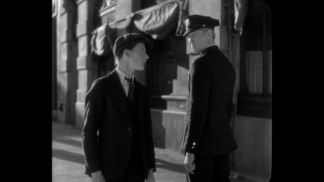 A teenage boy (Junior Durkin) introduces himself to a policeman