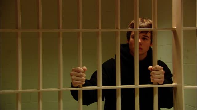 MS Teenage boy looking worried as he grips bars in prison cell/ New Jersey