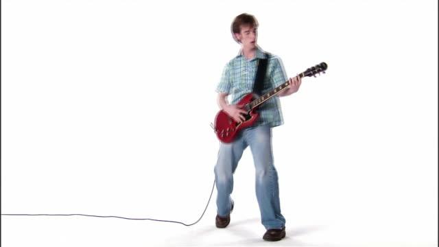 WS, teenage boy playing electric guitar, studio shot