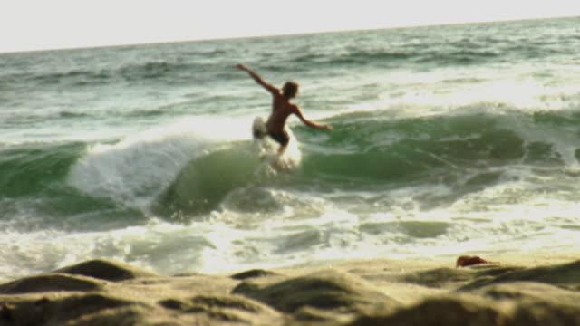 WS Teenage boy (14-15) skim boarding on beach / Laguna Beach, California, USA