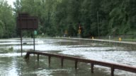 Teenage boy walks on guard rail of flooded Bronx River Parkway Zoom out to reveal WS of flooded area Bronx River Parkway Flooded on August 28 2011 in...
