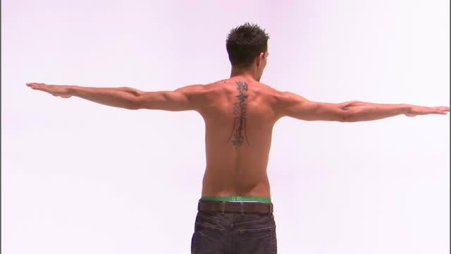 MS Teenage boy (14-15) with tattoo dancing, against white background / Orem, Utah, USA