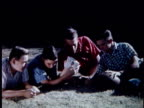 MS Teenage boys and young men listening to radio and lying on grass, then they cheer / USA