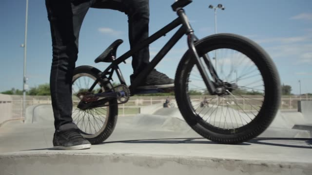 Teenage boys doing BMX tricks in skate park