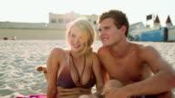 Teenage couple on a beach in sunlight